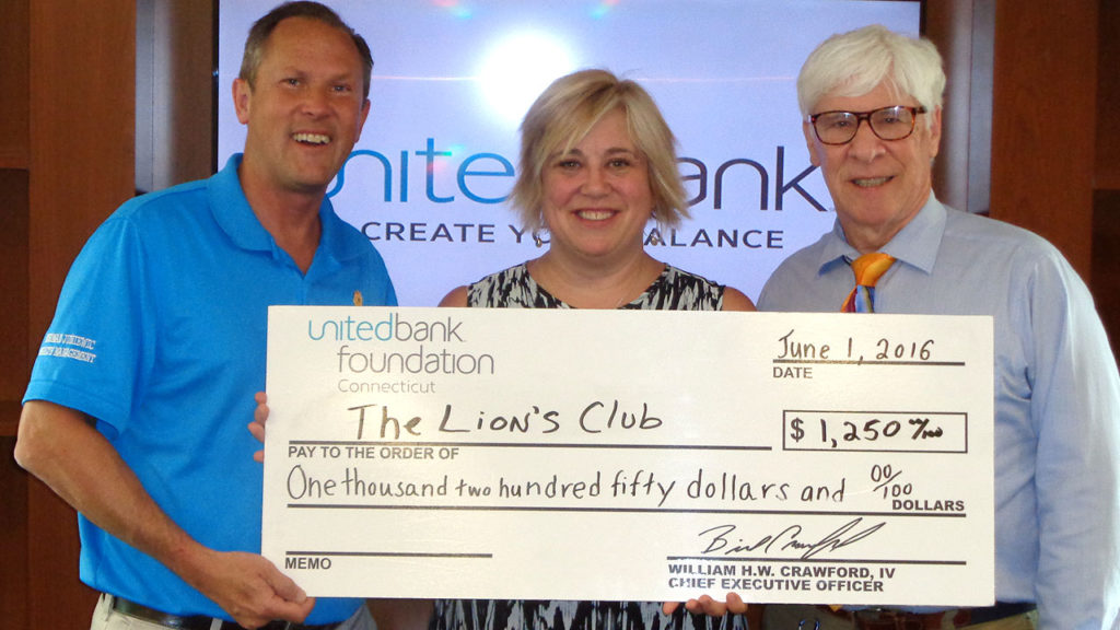 Kathy Larkin (center) from United Bank presents a check for $1,250 to Norman Juniewic and Alan Shultz from the Lion's Club.