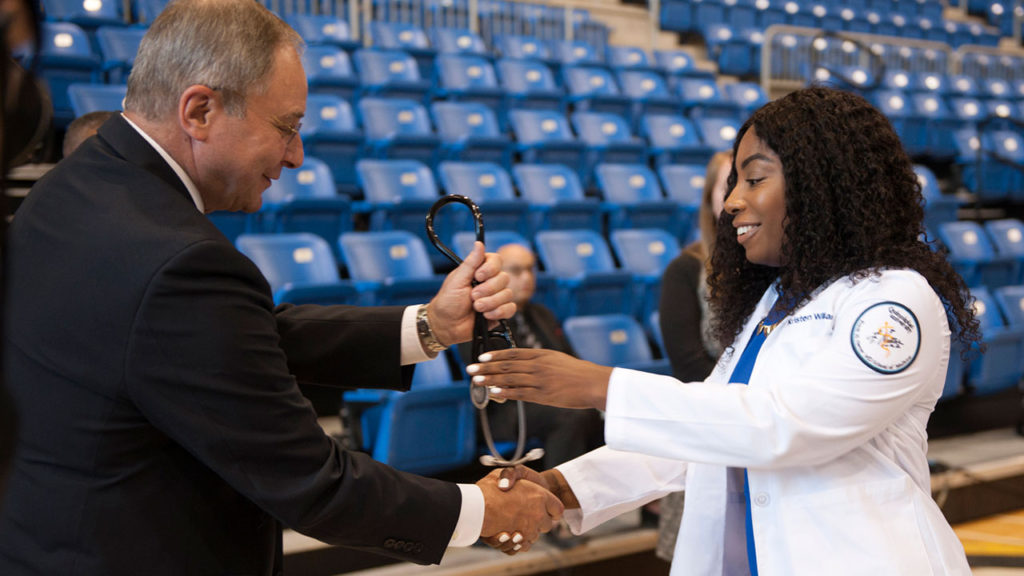 Dr. Bruce Koeppen, dean of the Frank H. Netter MD School of Medicine at Quinnipiac University, presents a stethoscope to first-year medical student Kristen Williams on Aug. 4, at the medical school's annual White Coat ceremony.