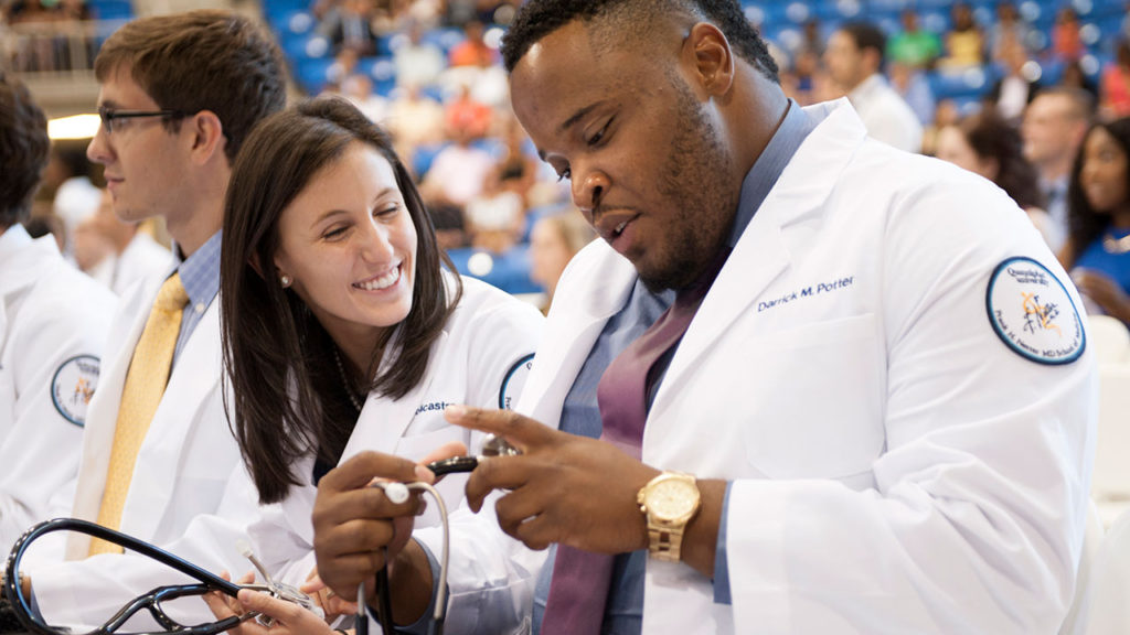 Quinnipiac University first-year medical students, from left, Alexa Policastro, of Saddle River, New Jersey, and Darrick Potter, of New Haven, check out their new stethoscopes during the Frank H. Netter MD School of Medicine's White Coat Ceremony on Aug. 4 at the TD Bank Sports Center on the university's York Hill Campus.
