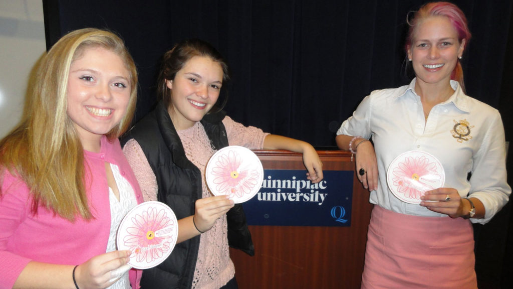 "From left Quinnipiac University School of Nursing students Emily Kata, left, and Jordan LaCross, co-presidents of the Quinnipiac Student Nurses Association, and Betsy Nilan. president of the ""Get in Touch Foundation"" discuss the Daisy Wheel, which helps to teach girls in grades five-12 about the importance of and techniques for conducting breast self-exams."